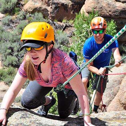 A young woman rock climbs
