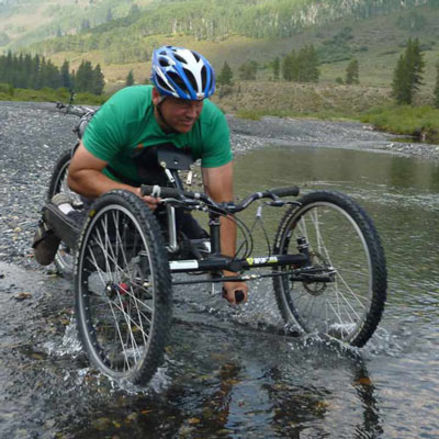 Man rides cross country bike through a stream