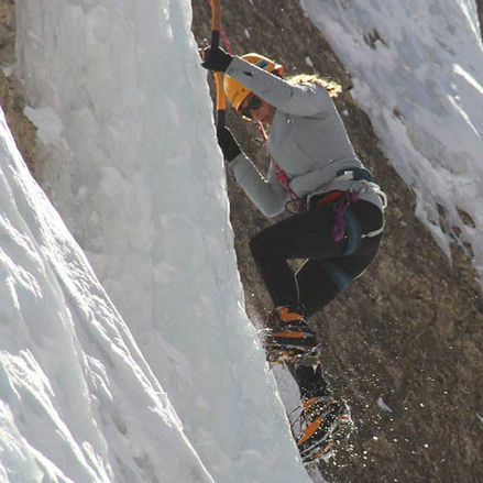 Woman climbing up a wall of ice