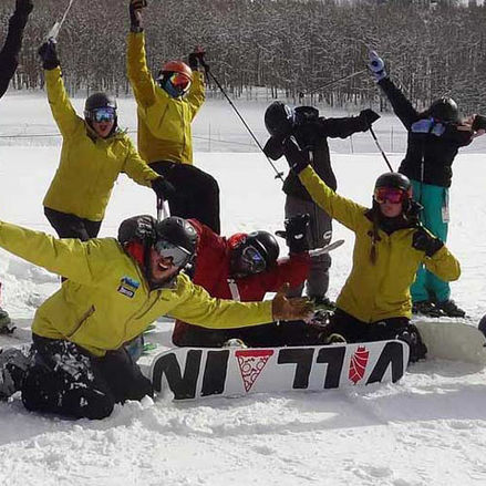 Group of skiers and snowboarders in front of a mountain