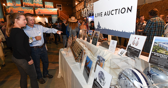 People look at live auction items at the Crested Butte Open fundraising gala.