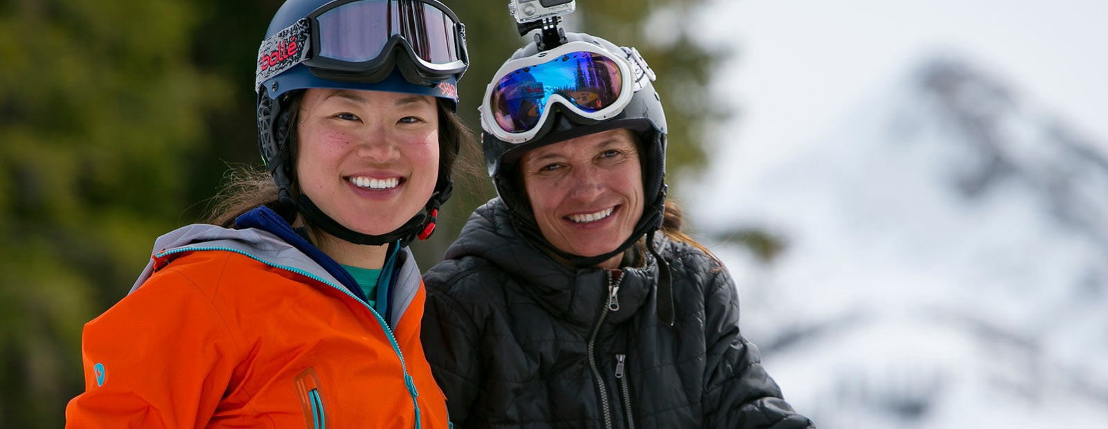 Two women skiers smiling