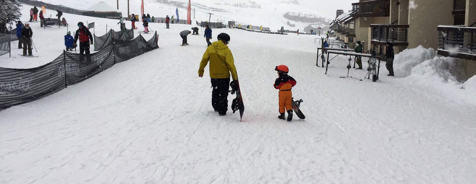 Instructor and child snowboarder walk by the ski lodge