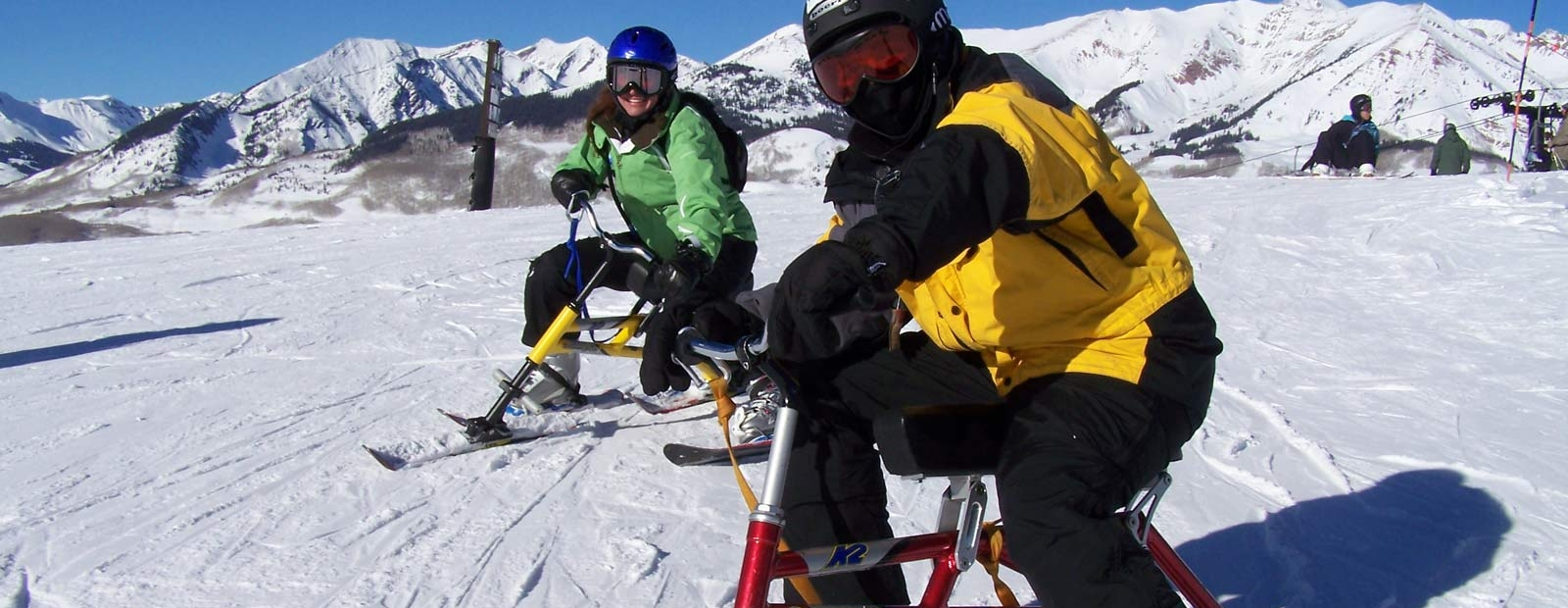 Two people on ski bikes going down a snow-covered slope