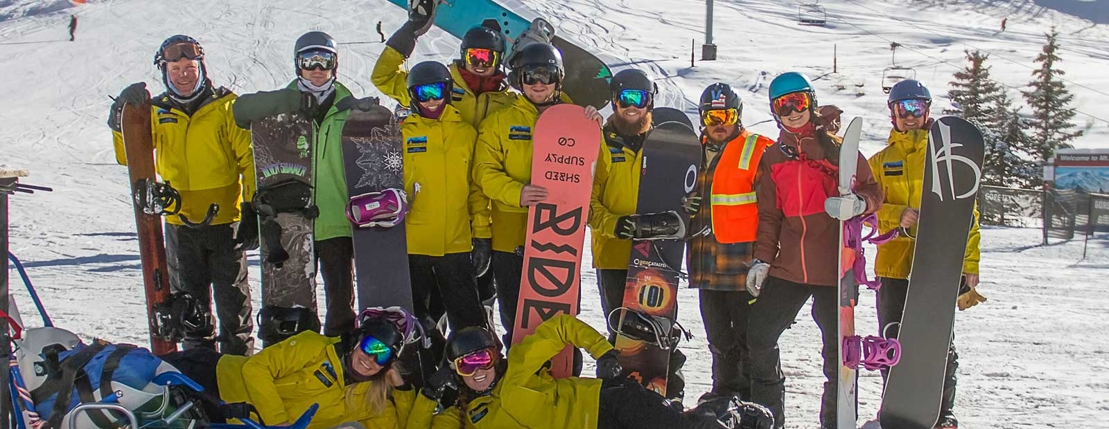 Group of snowboarders on top of a mountain