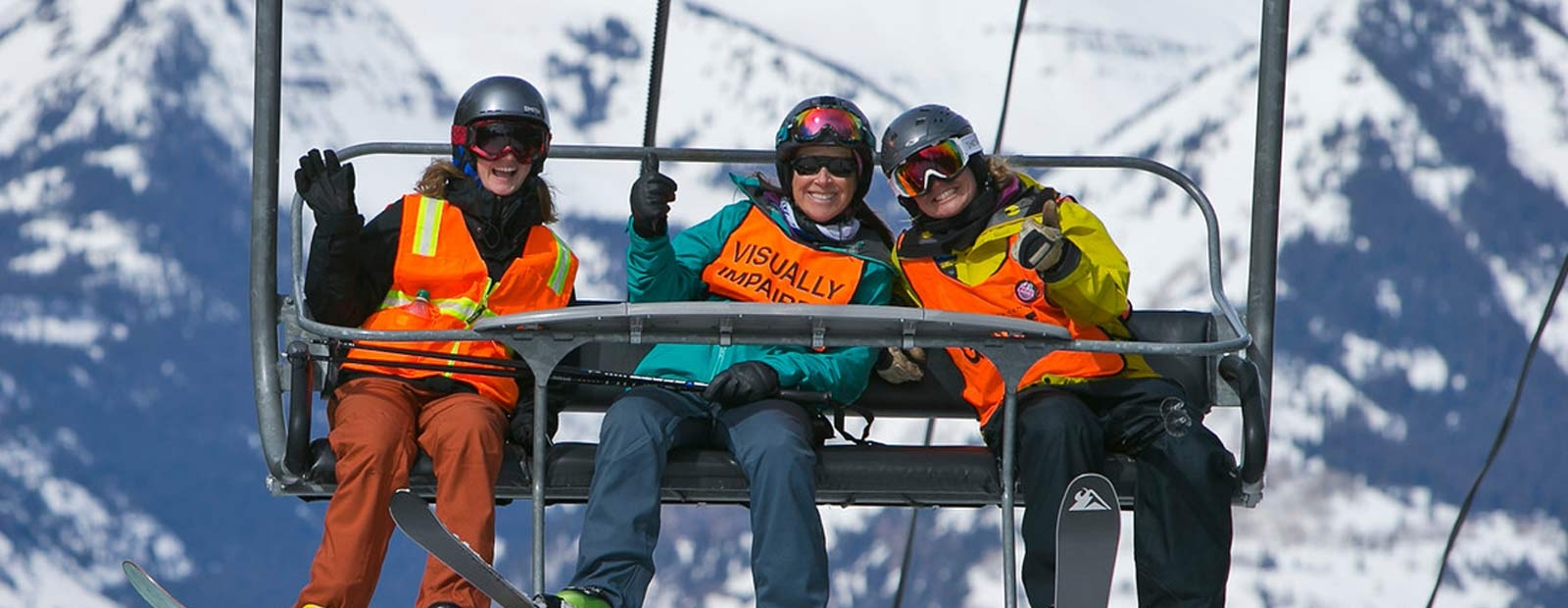 Three people riding up a ski lift to the top of a snow covered mountain